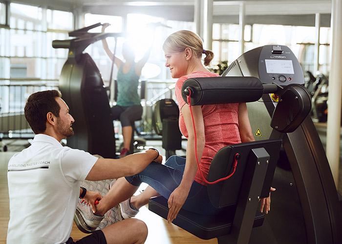 Frau trainiert mit Trainer im Milon Zirkel