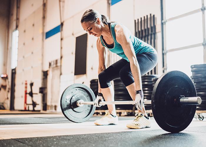 Sportliche Frau trainiert mit schweren Gewichten im Athletic Center