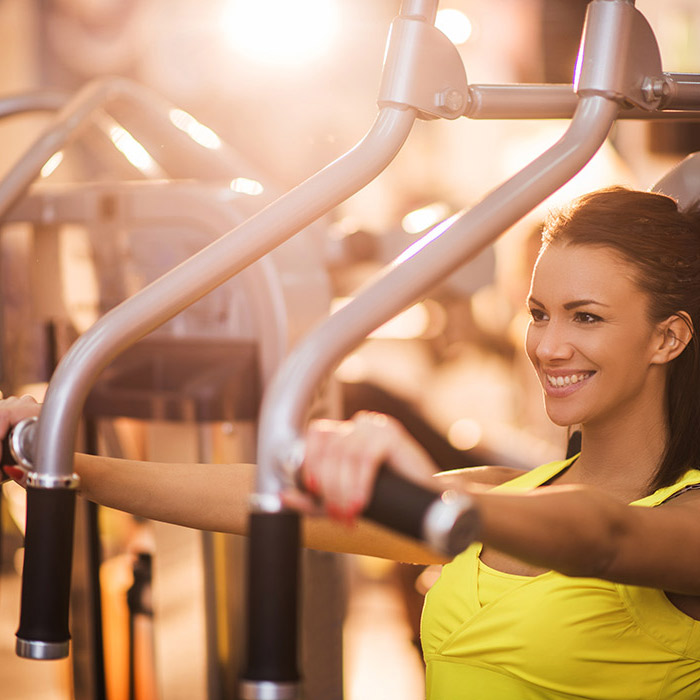 Junge Frau trainiert ihre Muskulatur im Fitnessstudio