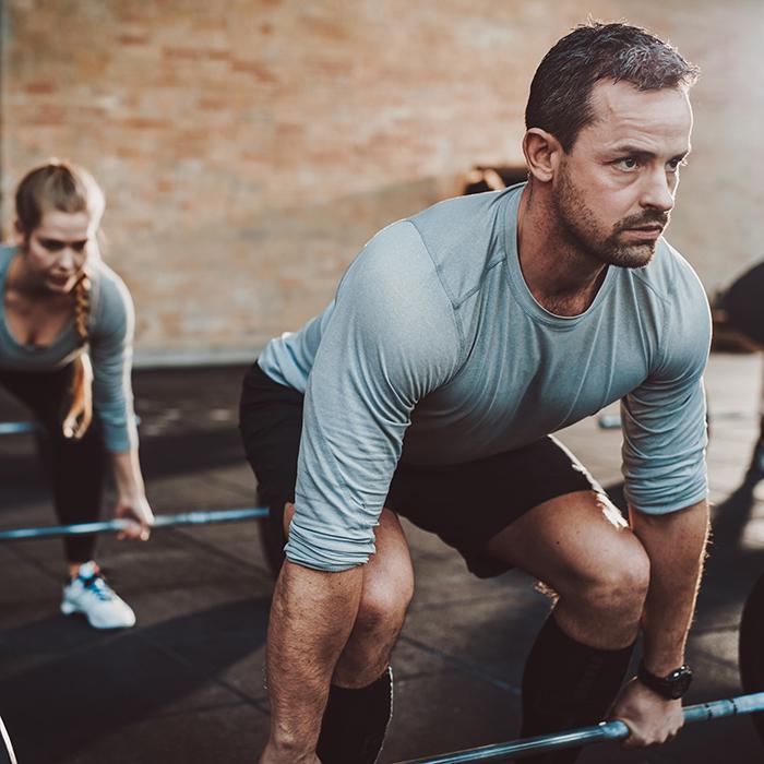 Mann trainiert im Gruppenkurs seine Kraft und seine Figur
