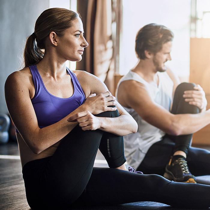 Paar dehnt nach dem Training seine Muskulatur