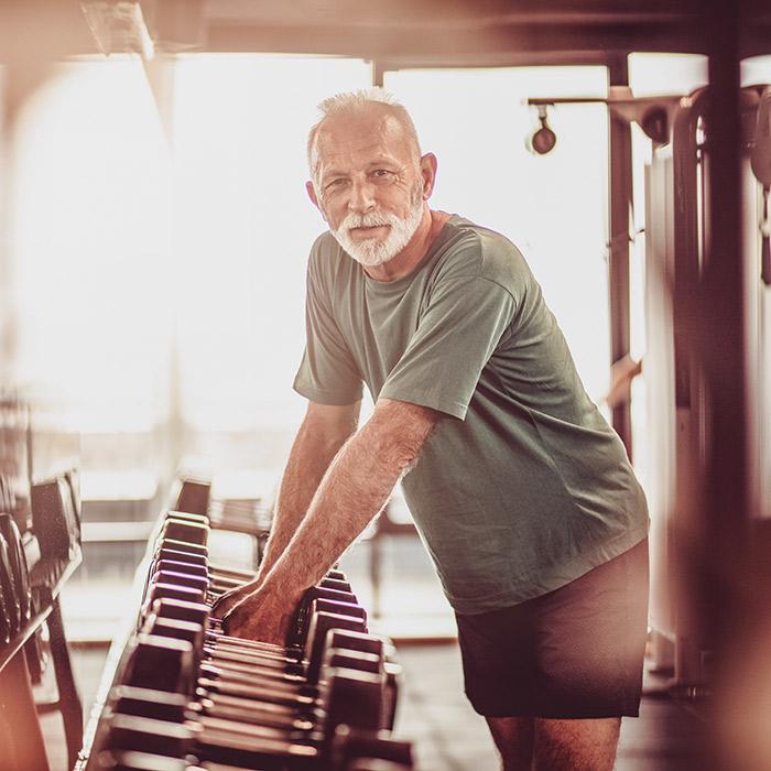 Alter Mann trainiert seine Fitness mit freien Gewichten