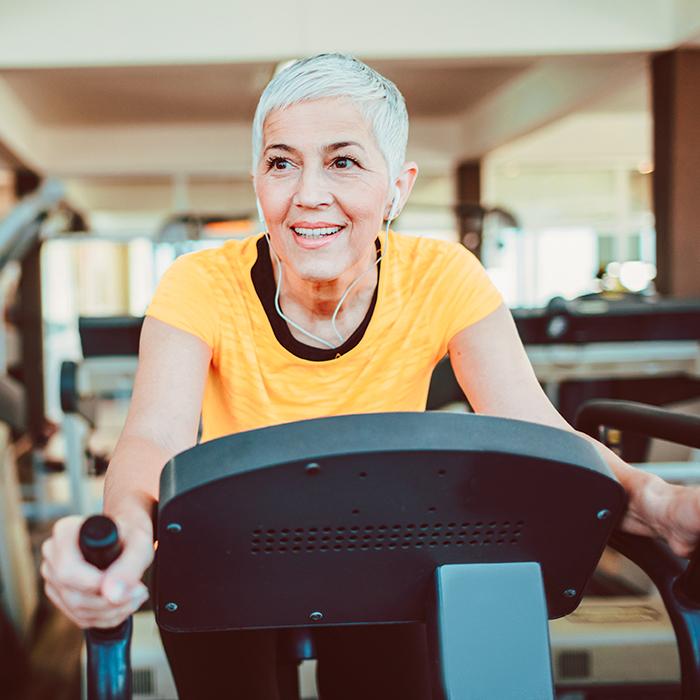 Attraktive ältere Frau trainiert ihre Ausdauer im Fitnessstudio