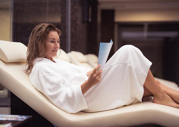 Frau liest und entspannt im Wellnessbereich nur für Frauen