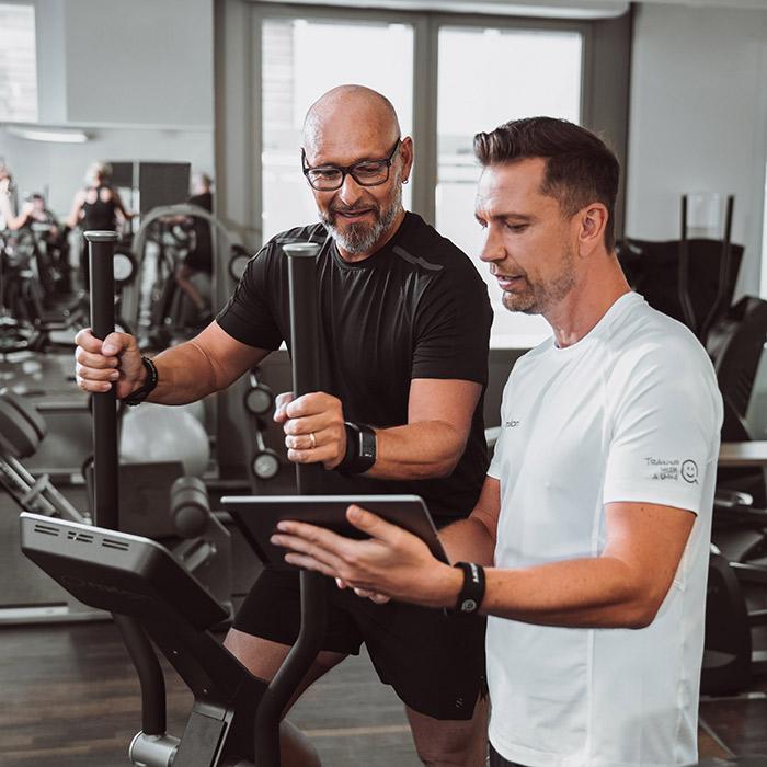 Mann trainiert mit Trainer im Milon Fitnesszirkel
