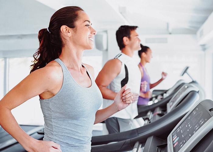 Glückliche Frau trainiert im Fitnessstudio Rückgrat auf dem Laufband