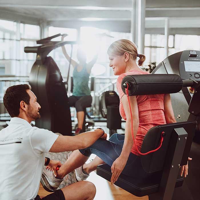 Frau trainiert im Woman mit ihrem Fitnesstrainer im Milon Zirkel
