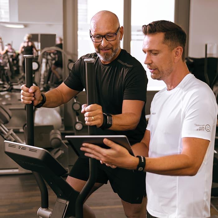 Mann trainiert mit Trainer im Milon Zirkel